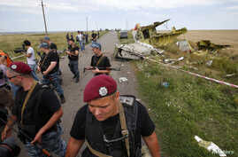 Armed pro-Russian separatists stand guard at a crash site of Malaysia Airlines Flight MH17, near the village of Hrabove, Donetsk region, July 20, 2014.