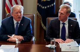 FILE - In this April 9, 2018 photo, Deputy Secretary of Defense Patrick Shanahan, right, listen as President Donald Trump speaks during a cabinet meeting at the White House, in Washington.