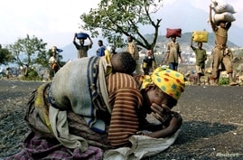 A Rwandan woman collapses with her baby on her back alongside the road connecting Kibumba refugee camp and Goma, July 28, 1994.