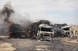 Afghan firefighters spray water on burning NATO supply trucks in Samangan, north of Kabul, Afghanistan, July 18, 2012.