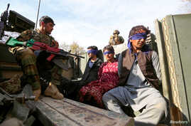 FILE - Taliban militants, who were arrested by Afghan security forces, sit on a vehicle, during a presentation to the media, in Jalalabad, Afghanistan, March 17, 2018.