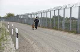 FILE - A police officer with a dog patrols the border fence on the Hungarian-Serbian border near Roszke, 180 kms southeast of Budapest, Hungary, April 28, 2017. Hungary has asked the EU to pay half of the cost of the fence built to keep illegal immig...