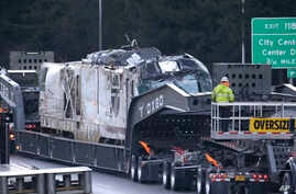 The engine from Monday's Amtrak train crash onto Interstate 5 is transported from the scene, Dec. 20, 2017, in DuPont, Wash. Three men were killed as a result of the derailment, which occurred after the train barreled into a 30-mph zone at 80 mph.