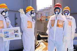 Japan's Prime Minister Shinzo Abe (2nd R), wearing protective suit and mask, is briefed about tanks containing radioactive water by Fukushima Daiichi nuclear power plant chief Akira Ono (2nd L), as they stand near a tank (C, with railings painted red