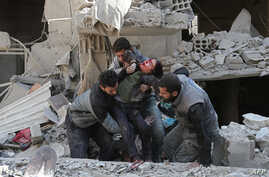Syrians rescue a child following a reported regime air strike in the rebel-held town of Hamouria, in the besieged Eastern Ghouta region on the outskirts of the capital Damascus, Feb. 21, 2018.