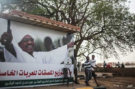 """Sudanese boys walk past an election campaign banner in support of President Omar al-Bashir that reads """"community commission in support of nominating Marshal Omar al-Bashir, in Khartoum, Sudan, April 11, 2015."""
