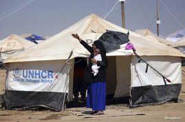 A woman, who fled from violence in Mosul, carries a baby in a camp edging Irbil in Iraq's Kurdistan region June 25, 2014.