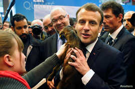 French President Emmanuel Macron holds a young goat as he visits the 55th International Agriculture Fair in Paris, Feb. 24, 2018.