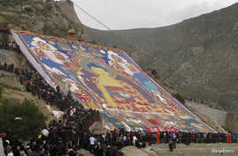 Tibetan Buddhists and tourists view a huge Thangka, a religious silk embroidery or painting displaying the Buddha portrait, during the Shoton Festival at Zhaibung Monastery in Lhasa, capital of southwest China's Tibet Autonomous Region, August 17, 20