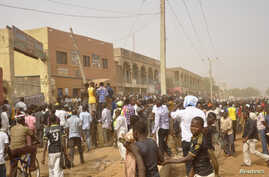 People rush to the scene of explosions at a bus park in Sabon Gari, where the Islamist sect Boko Haram is waging an insurgency against the government, in Kano, Nigeria, March 19, 2013.