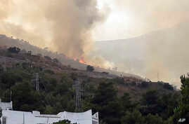 A fire burns behind a tourist resort which was then successfully evacuated, in the Sicilian area of San Vito Lo Capo, near Trapani, southern Italy, July 12, 2017.