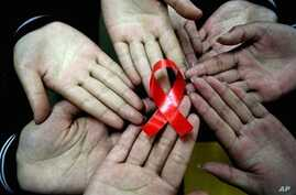 Chinese students show a handmade red ribbon one day ahead of the the World AIDS Day, 30 Nov 2009