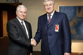 FILE - U.S. Defense Secretary Robert Gates, left, shakes hands with Ukrainian Defense Minister Mykhailo Yezhel  at NATO headquarters in Brussels, June 10, 2010. Belarus has granted Yezhel refugee status.