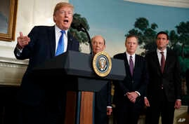 President Donald Trump speaks before signing a presidential memorandum on the imposition of tariffs and investment restrictions on China, in the Diplomatic Reception Room of the White House,  March 22, 2018, in Washington. From left are Trump, Secret