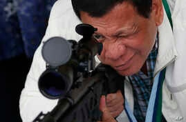 In this June 28, 2017 photo, Philippine President Rodrigo Duterte checks the scope of a Chinese-made CS/LR4A sniper rifle.