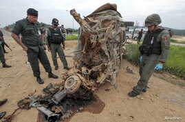 FILE - Military personnel stand next to a damaged military vehicle where soldiers were attacked by suspected Muslim militants at Muang district in the southern province of Yala, Thailand, Sept. 4, 2015.