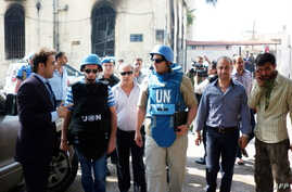 A team of United Nations observers tour the Syrian town of al-Haffe in the Mediterranean province of Latakia with an official Syrian security escort, June 14, 2012. (AFP/SANA)