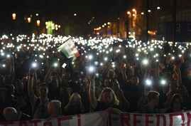 Protesters hold up lit mobiles phones during a rally against legislation that could force the closure of the Soros-founded Central European University, in front of Parliament, in Budapest, Hungary, April 2, 2017.