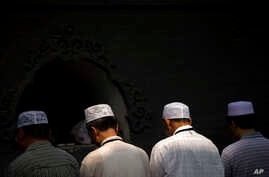 FILE - Chinese Hui Muslims pray during Eid al-Fitr prayers at Niujie Mosque in Beijing, July 18, 2015. Authorities in northwestern China were poised to begin demolition of a mosque Friday, despite protests by hundreds of members of the country's Musl...