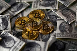 Bitcoin (virtual currency) coins placed on Dollar banknotes are seen in this illustration picture, Nov. 6, 2017.