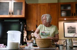 Anne Hunt, who was diagnosed woth Alzheimers in 2016, looks to her husband, Bruce, to be reminded if she already added sugar to her dough in their home in Chicago, Illinois, July 13, 2018.