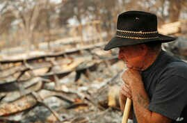 Ed Bledsoe rests as he searches through what remains of his home, Aug. 13, 2018, in Redding, Calif. Bledsoe's wife, Melody, great-grandson James Roberts and great-granddaughter Emily Roberts were killed at the home in the Carr Fire.