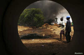 Oil workers, seen through a pipe, look on at the scene of an oil pipeline fire in Dadabili, Niger state, April 2, 2011.