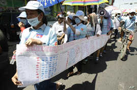 Cambodian protesters from Boueng Kak lake march with a banner displaying the thumb prints of fellow land owners who have been evicted from their homes, as they demand compensation, in Phnom Penh, Cambodia.