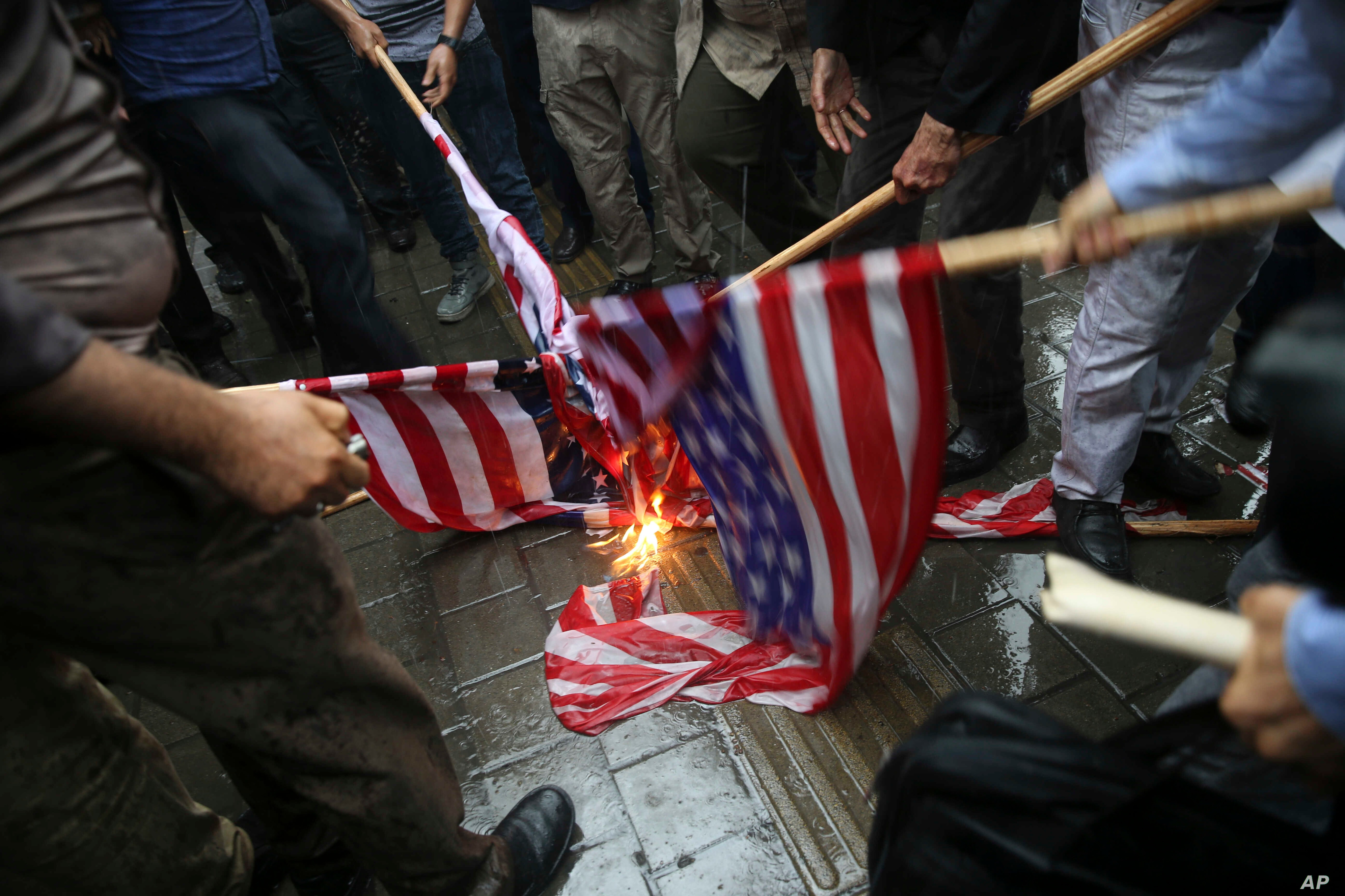 Iranian demonstrators burn representations of the U.S. flag during a protest in front of the former U.S. Embassy in response to President Donald Trump's decision to pull out of the nuclear deal and renew sanctions, in Tehran, Iran, May 9, 2018.