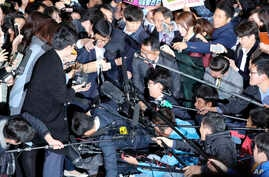 Choi Soon-sil, center left wearing black hat, a cult leader's daughter with a decades-long connection to President Park Geun-hye, is surrounded by prosecutor's officers and media at the Seoul Central District Prosecutors' Office in Seoul, South Korea