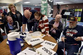 FILE - Voters sign in to cast their ballots during the Nevada Republican presidential caucus at Western High School in Las Vegas, Nevada.