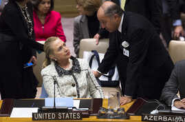 United States Secretary of State Hillary Clinton speaks to French Foreign Minister Laurent Fabius before a meeting of the Security Council during the 67th United Nations General Assembly, at U.N. headquarters in New York, September 26, 2012.