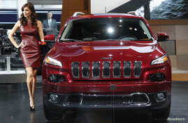 A model poses next to a Jeep Cherokee during the press preview day of the North American International Auto Show in Detroit, Michigan January 14, 2014. REUTERS/Rebecca Cook (UNITED STATES  - Tags: TRANSPORT BUSINESS)   - RTX17DUM