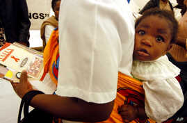 FILE - A mother carries a child on her back as she visits an exhibition on HIV/AIDS in Gaborone, Botswana.