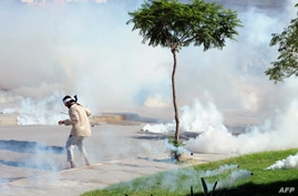 A Tunisian protester is engulfed in tear gas smokes during a protest outside the U.S. embassy in Tunis against a film mocking Islam, September 14, 2012.