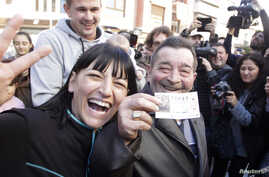 """Juan Lopez holds his lottery ticket with the winning number of Spain's Christmas Lottery """"El Gordo"""", together with his daughter Pilar in La Eliana near Valencia, Dec. 22, 2014."""