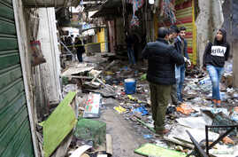 Iraqi security forces inspect the site of a bomb attack at a market in central Baghdad, Iraq, Dec. 31, 2016