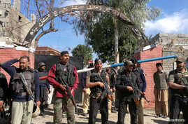 Policemen stand guard at a courthouse after an attack by suicide bombers in Charsadda, Pakistan, Feb. 21, 2017.