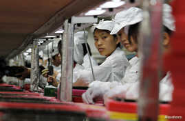 FILE - Workers are seen at a Foxconn factory in Longhua, Guangdong province, China, May 26, 2010. Foxconn is Apple's main supplier of iPhones.