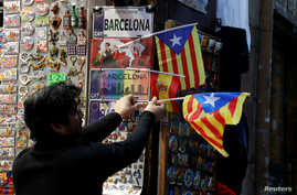 """A shop keeper displays Catalan separatist """"Estelada"""" flags next to souvenirs for tourists at a shop in Barcelona, Dec. 22, 2017."""