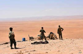 This photo released Sept 2, 2017, by the Syrian official news agency SANA, shows Syrian troops and pro-government gunmen standing guard at one of the frontline hills where they are fighting IS militants in Deir el-Zour, Syria.
