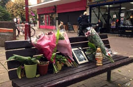 In this photo taken Oct. 20, 2016, flowers and candles are seen at a memorial to Arkadiusz Jozwik in Harlow, England. On Aug. 27, Arkadiusz Jozwik, an immigrant from Poland known as Arek, died following an altercation with youths outside a local pizz