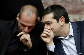 Greece's Prime Minister Alexis Tsipras chats with Greece's Finance Minister Yanis Varoufakis during a Presidential vote in Athens, on Wednesday, Feb. 18, 2015.
