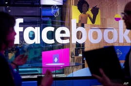 FILE - Conference workers speak in front of a demo booth at Facebook's annual F8 developer conference, in San Jose, California, April 18, 2017.