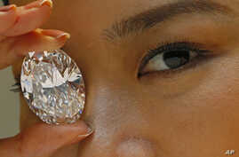 A 118.28-carat white diamond is displayed by a model at a press preview at Sotheby's auction house, Thursday, Sept. 19, 2013 in Hong Kong. The oval stone will be auctioned off in Hong Kong on Oct. 7 and has a pre-sale estimate of US$28 million to $35