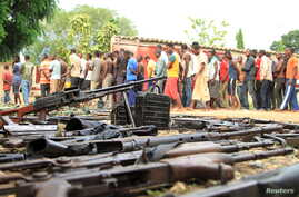 Suspected fighters are paraded before the media by Burundian police near a recovered cache of weapons after clashes in the capital, Bujumbura, Dec. 12, 2015.