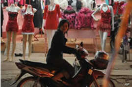 A woman stops her motorbike outside a shop in Vientiane, 18 Dec 2009
