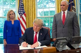 President Donald Trump signs an executive order to keep families together at the border, but says that the 'zero-tolerance' prosecution policy will continue, during an event in the Oval Office of the White House in Washington.