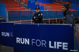 A NYPD officer stands guard during the ceremonial painting of the New York City Marathon blue line at Central Park in New York, October 30, 2013. More than 45,000 runners will race through the streets of New York City on Sunday. REUTERS/Eduardo Munoz