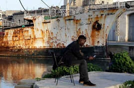 FILE - A migrant uses his mobile phone as he sits on a dock of Valletta harbor, Malta, Feb. 2, 2017.